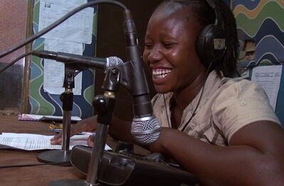 A smiling African woman wearing headphones and facing a microphone in a radio station.
