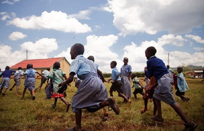 African children cheerfully running in a schoolyard.