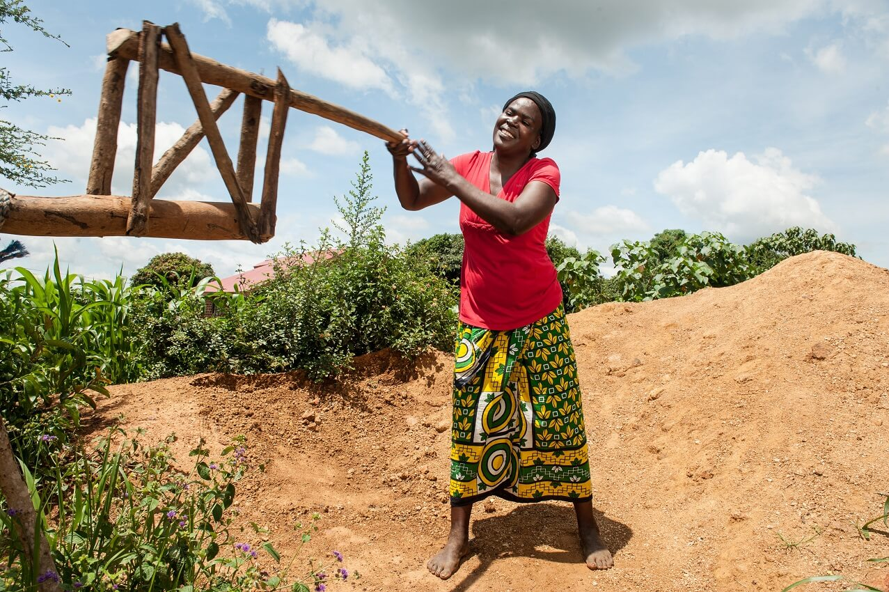 A smiling African woman holds onto a wooden fixture.