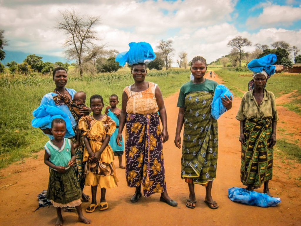 Four African women and four African children pose on a dirt road. Each of the women is carrying malaria nets.