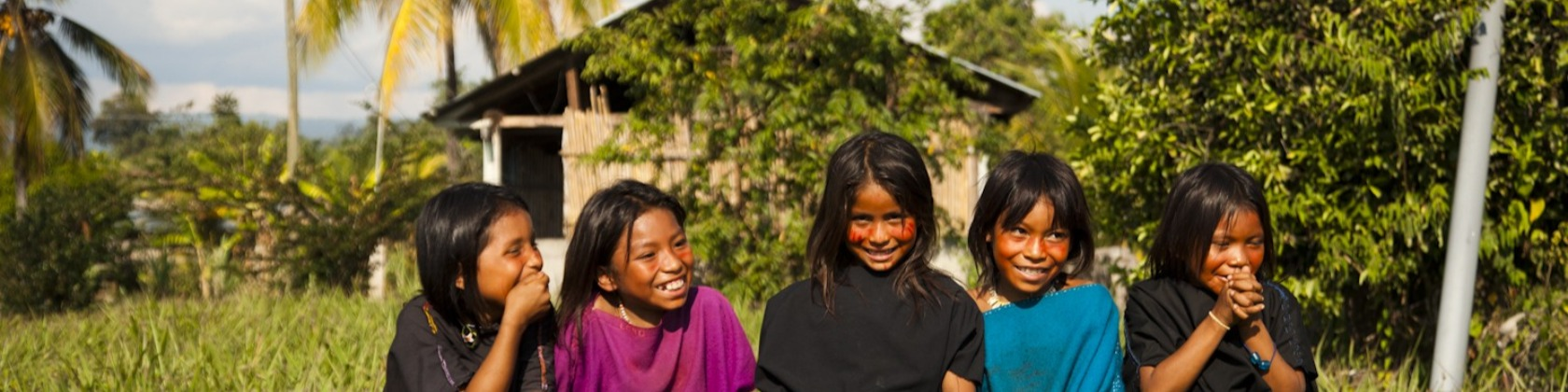Five indigenous children pose for a photo in front of their rural home