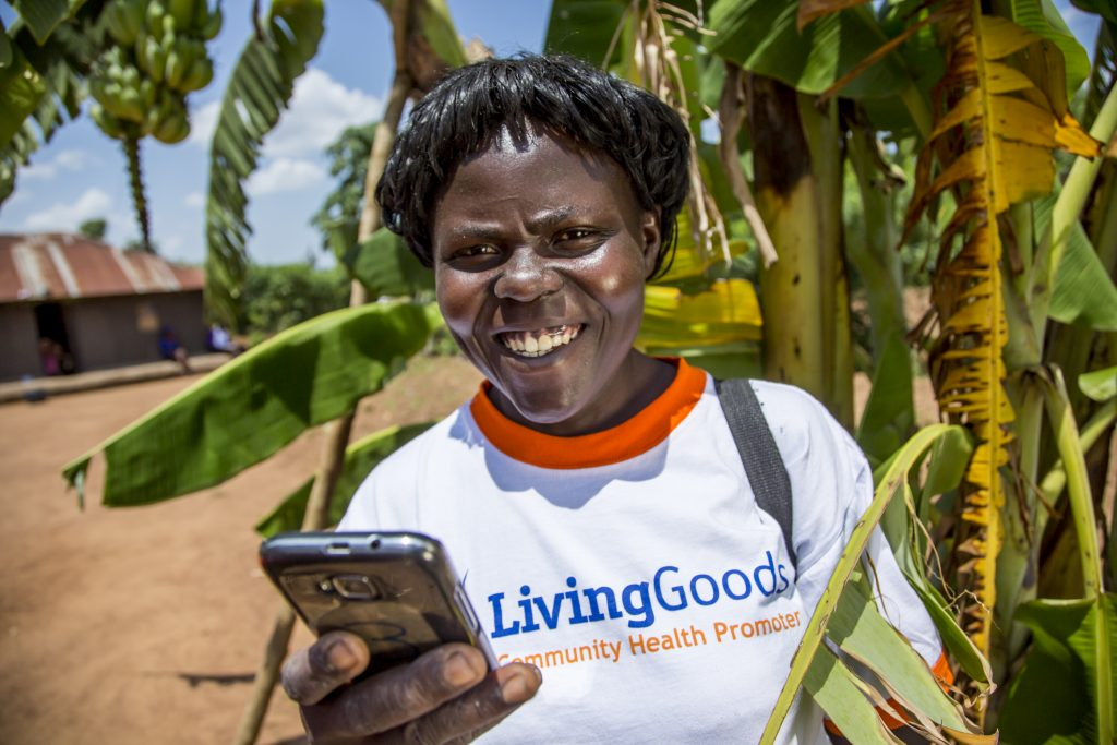 """An African woman wearing a shirt that says """"Living Goods: Community Health Promoter"""" looks up from phone and smiles."""