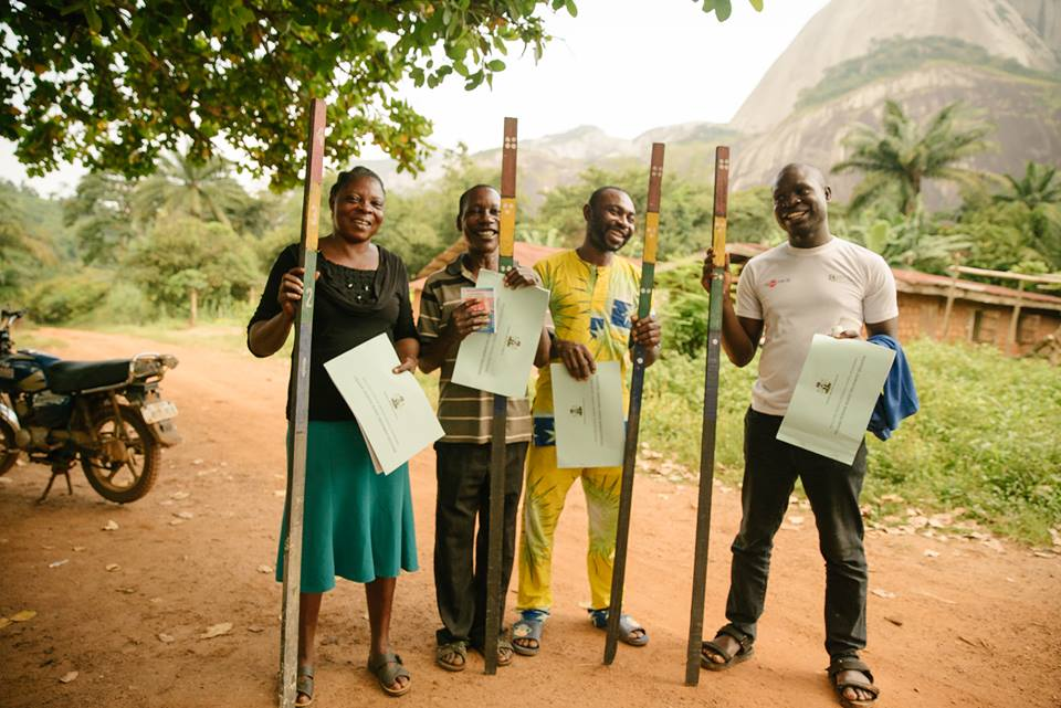 Four Africans smiling, holding certificates and measuring sticks on a dirt road.